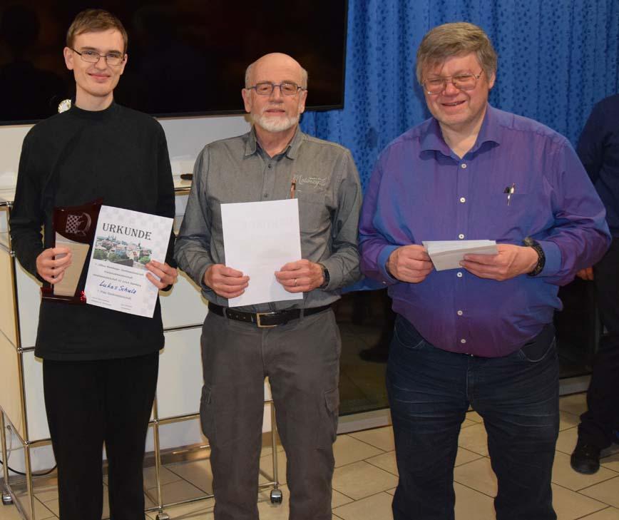 Lukas Schulz (links) erhält die Siegertrophäe (v.l.: FM Lukas Köhler, Prof. Dr. Peter Krauseneck, Turnierleiter Erwin Ortlauf)